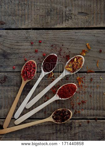 Red Spices On A Wooden Background. Pink Pepper, Sumac, Paprika, Marigold, Sichuan Pepper.