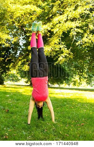 fitness girl doing a handstand in the park