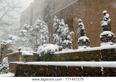 It's snowing rather heavily in Manhattan. Statues and trees covered with snow.