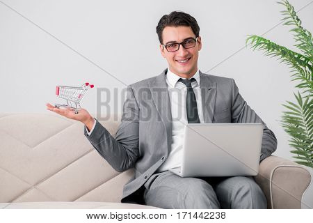 Businessman with laptop and shopping cart
