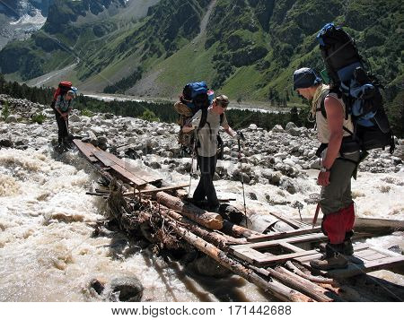 CAUCASUS, RUSSIA - AUGUST 6, 2007: The climbers are crossing a flashy mountain river over the old wooden bridge in the gorge Adyr-Su. Caucasus Russia.