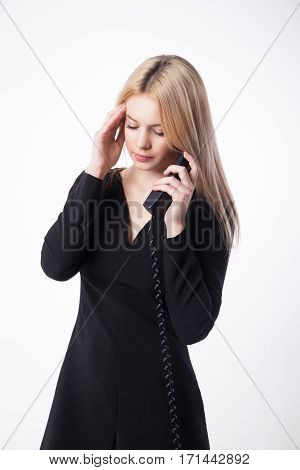 Portrait unhappy young woman talking on phone looking down isolated on white