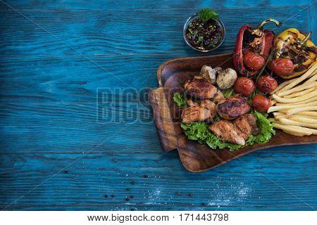 Grilled pork meat with vegetable on a blue wooden background