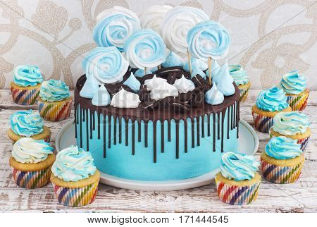 Children's blue cake and cupcakes rainbow color on a white background with wood meringue