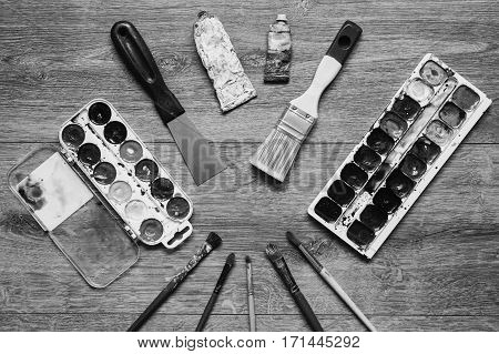 Black and white art photography monochrome artistic squirrel brushes tubes of oil paints and watercolors on a wooden background.The palette of twenty-four colors .Used tools for artists