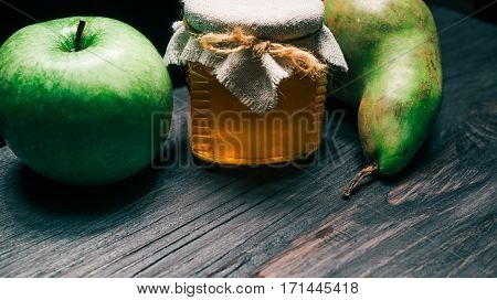 Little honey jar next to big green pear and apple on black wood