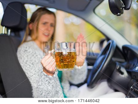 Careful woman driver at the car wheel refusing jug with alcoholic drink.