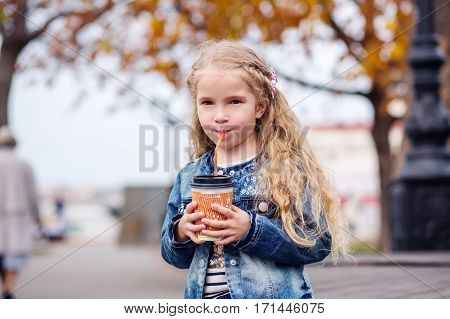 Little happy girl drinking cocoa out of the straw