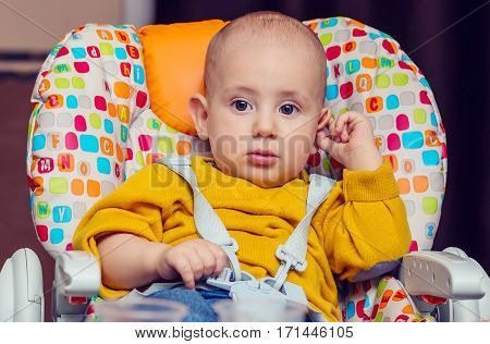 portrait of a little boy in a highchair. Hold the ear
