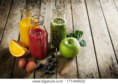 Tasty colorful fresh homemade smoothies in glass jars on wooden table. Healthy detox concept.