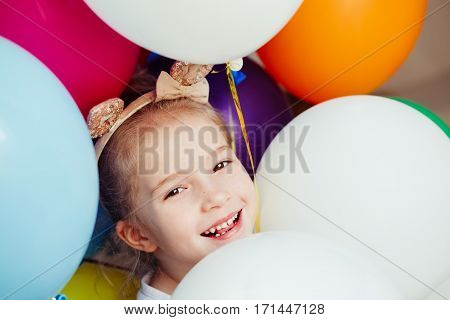 Happy little girl with colorful balloons plays