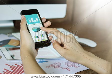 Business Concept. Woman's Hands Using Smart Phone With Financial Document.