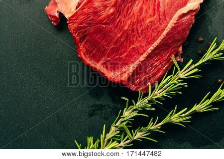 raw beef meat with spices on slate stone kitchen board.