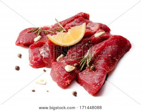 Pieces of meat with garlic and rosemary isolated on white background. Raw beef. Meat.