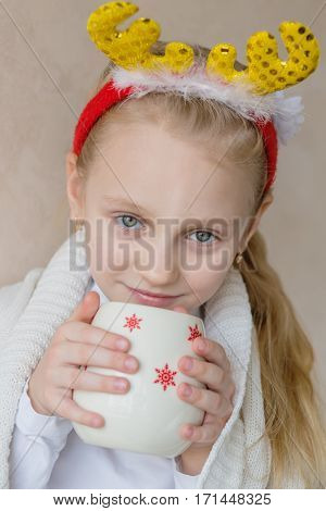 Charming little girl waiting for Christmas on a light background
