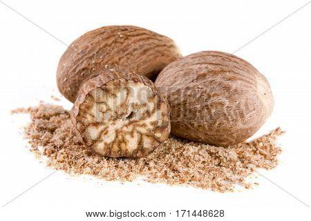 Three nutmeg and powder isolated on white background.