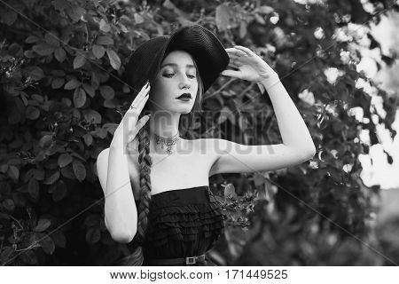 Black and white art photography monochrome girl with and pale skin in hat and dress with belt. Woman with long plait against the backdrop of bush roses. Necklace around his neck. Bright unusual appearance.