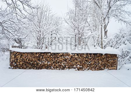 Firewood Logs Covered with Snow. Winter Pattern Background.