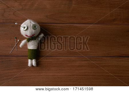 Cute Little Voodoo Doll with pins on wooden background.Copy space