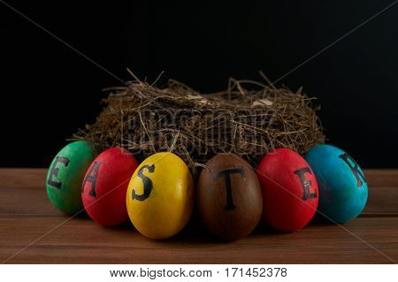 Easter holidays tradition and object concept - close up of colored easter eggs and quaill eggs in nest on wooden surface.black background