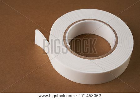 White double sided tape on light-brown background with copy space.Close up.