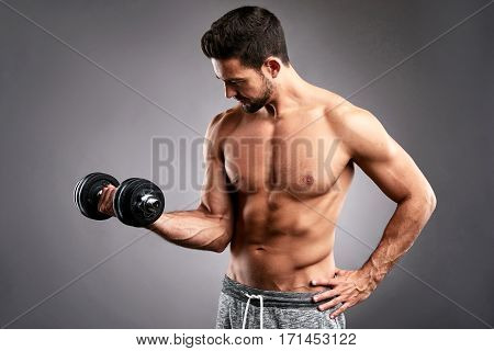 A half naked handsome young sportsman lifting a dumbbell with one hand