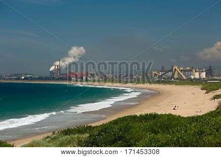 Beach of Wollongong, Australia with industrial facilities and coal piles in the background