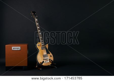 Combo amplifier for guitar with bass guitar on the black background with copy space