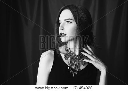 Black and white art photography monochrome beautiful girl in black unbuttoned jacket with red lips on dark background looking at the camera. Fashion photography. Bright appearance.