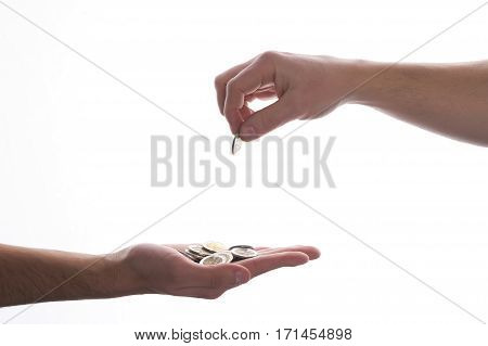 Human hand giving golden coin to another hand on isolated white background.