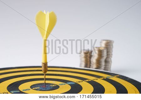Yellow dart hit in the center of a target with stack of coins behind on white background with copy space. A idea about money / currency investment that must decide or think carefully / thoroughly before putting money in these risky assets.