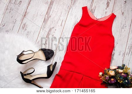 Red dress black shoes and bouquet. Imitation fur on a wooden background fashionable concept top view