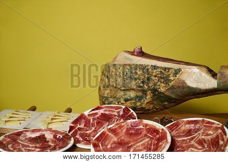 Smoked leg of lamb slised on white plate and cheese slices on wooden board with yellow background with copy space.