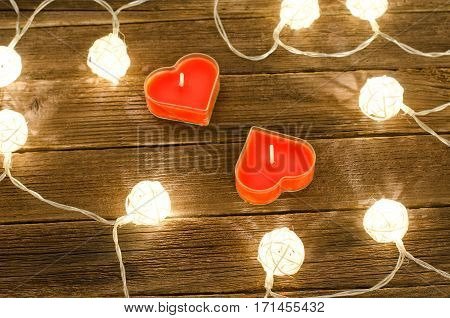 Two candles shape of heart among the glowing lanterns made of rattan on a wooden background. View from above