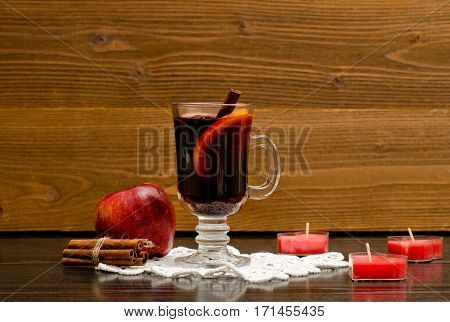 Mulled wine with spices on a lace napkin. Candles in the shape of a heart cinnamon sticks and apple. Wood background