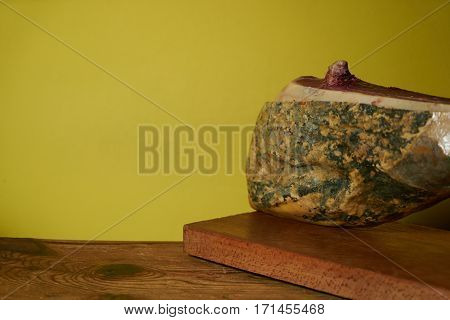 Smoked leg of lamb on wooden cutting board on yellow background with copy space.
