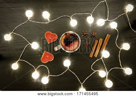 Candles in the shape of a heart mulled wine with spices cinnamon and anise. Rattan lanterns on black wooden table top view