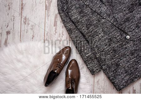 Brown patent leather shoes on a white fur gray coat a wooden background. Fashion concept. Top view space for text