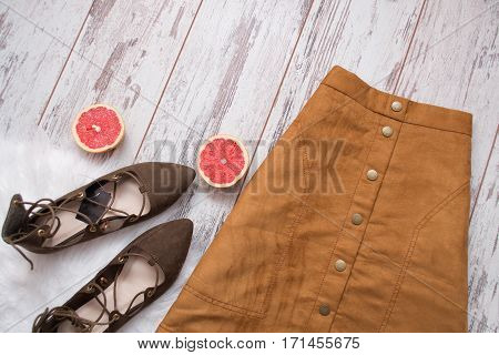 Brown suede skirt brown suede shoes cut grapefruit halves. Wooden background. Fashion concept. top view