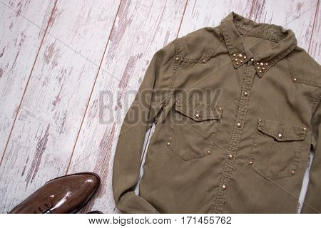 Khaki-colored shirt with rivets lacquered shoes. Wooden background space for text. Fashion concept. top view