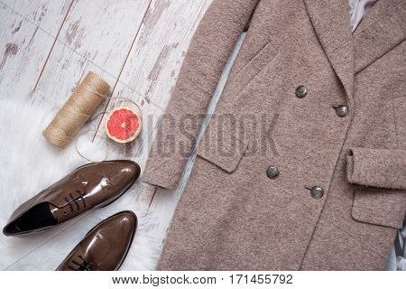 Brown coat and brown patent leather shoes on a white fur grapefruit and twine wooden background. Fashion concept. top view