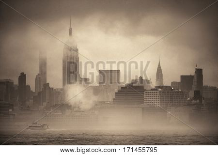 Midtown Manhattan skyscrapers and boat in fog in New York City