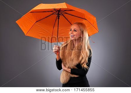 A beautiful young woman smiling and holding an umbrella wearing a stole