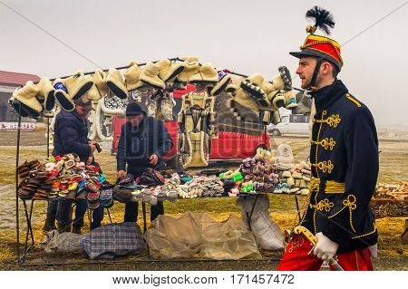 Hecha Ukraine - February 11 2017: A young man in the suit of the Hungarian hussar passes near a counter traders of slippers during the international gastronomic festival of butchers.
