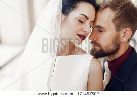 Elegant Stylish Groom Gently Embracing Gorgeous Bride In Light. Unusual Wedding Couple In Retro Styl