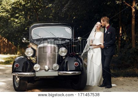 Luxury Elegant Wedding Couple Holding Hands On Background Of Stylish Black Car .  Gorgeous Bride And