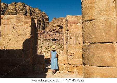 Photo of the Elegant female tourist in trendy hat and sky-blue dress explore lost rock city Petra. Romantic mood. Atmospheric place. Summer fashion style. Travel to Jordan. Adventure concept