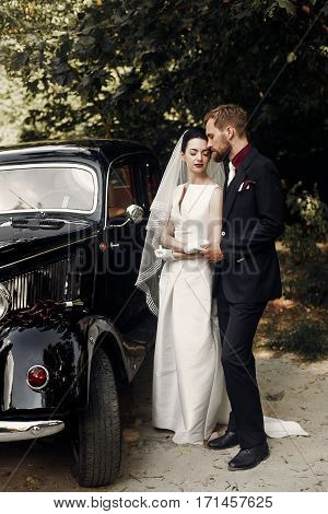 Luxury Elegant Wedding Couple Gently Embracing And Holding Hands On Background Of Stylish Black Car.
