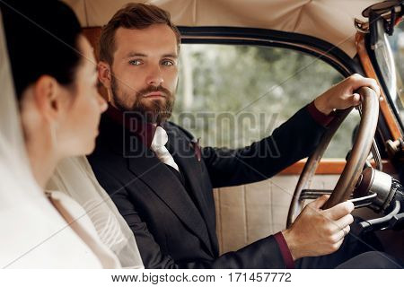 Luxury Elegant Wedding Couple Posing In Stylish Black Car. Handsome Groom Holding Helm  Looking At G