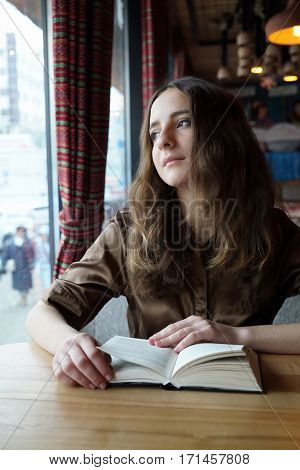 with book and looks in the window, thinking. Dark-brown eyes, mouth closed, natural make-up. Concept: romantic relationship, head in the clouds